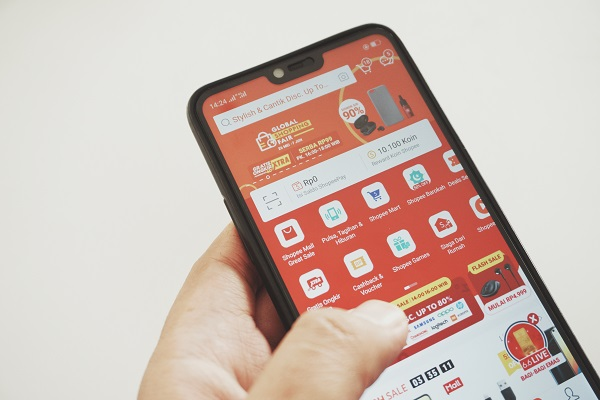 Tangan yang Sedang Memegang HP Handphone dengan Aplikasi Shopee Indonesia yang Terbuka di Layarnya