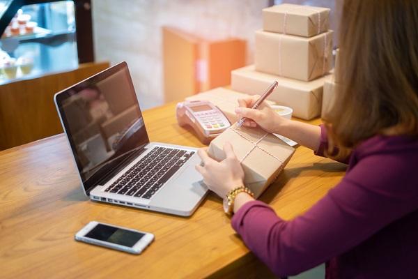 Seorang Perempuan Penjual Online atau Seller di Shopee yang Sedang Menulis Alamat Tujuan Pengiriman pada Box Paket Penjualan Berjualan Online di Hadapan Laptop
