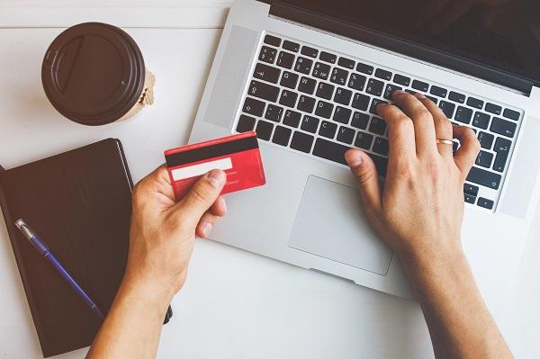 Tampilan Atas Tangan Pria yang Menggunakan Kartu Kredit untuk Belanja Online