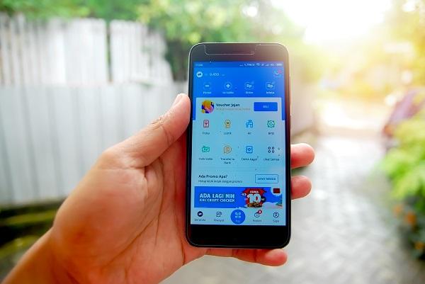 Tangan Seseorang yang Sedang Memegang HP Handphone dengan Aplikasi DANA Dompet Digital Indonesia yang Terbuka